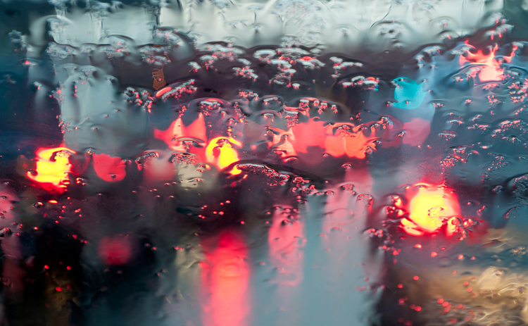 Blurred traffic lights through a rainy windscreen