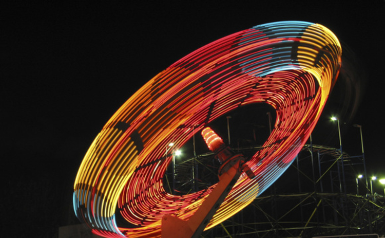 multicoloured-neon-spinning-fairground-ride-on-black-background