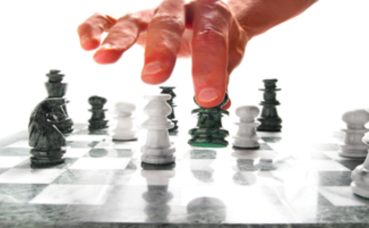 A hand moving chess pieces on a board
