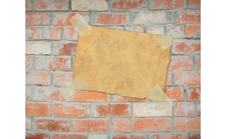 old-piece-of-paper-taped-onto-brick-wall