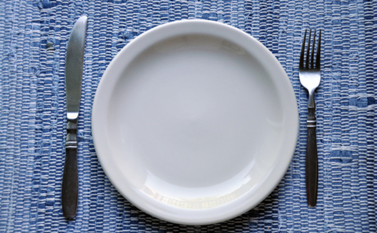 An empty plate flanked by a knife and fork