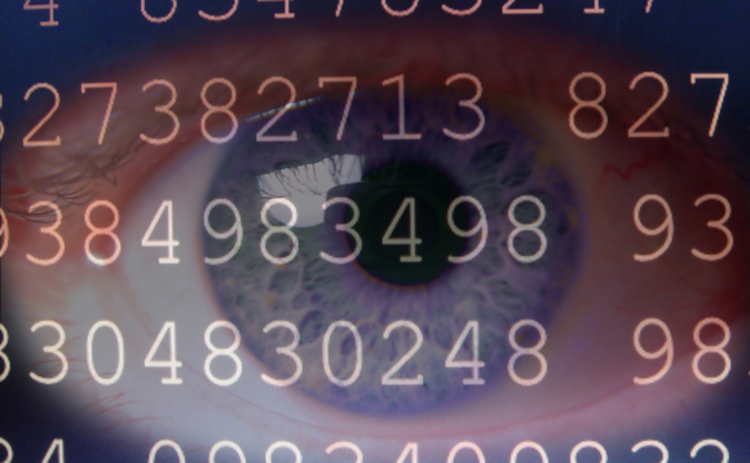 An eye in close-up superimposted by a screen of random numbers