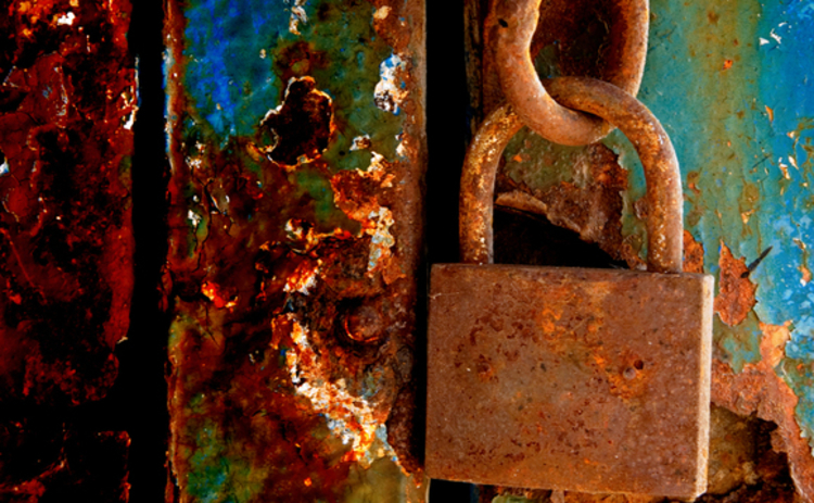 open-rusty-padlock-on-crumbly-painted-door