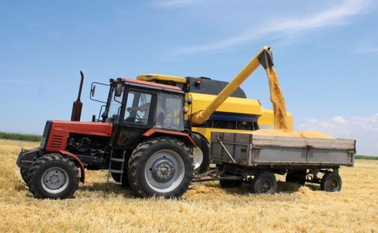 A tractor and combine harvester harvesting grain