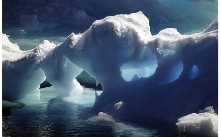 iceberg-arches-melting-into-freezing-blue-sea