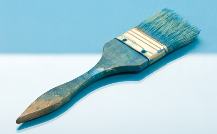 Blue paintbrush on two-tone blue background
