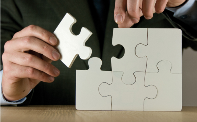 A man putting the final piece of a jigsaw together