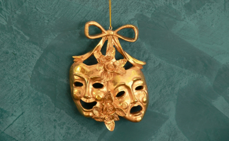 gold-comedy-tragedy-mask-hanging-on-green-background