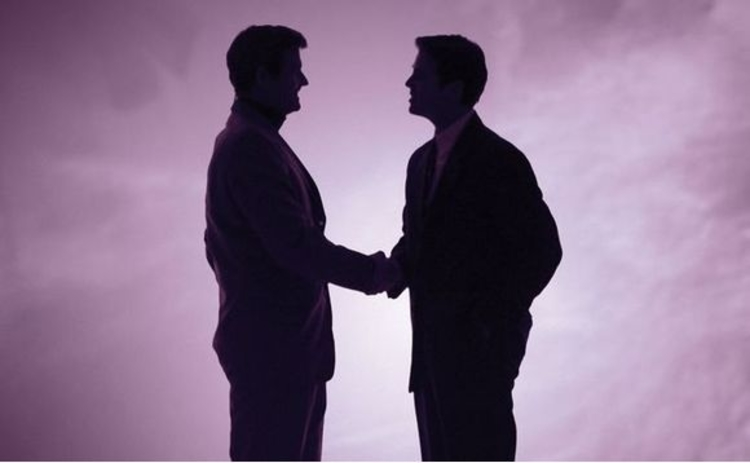 Two men shake hands