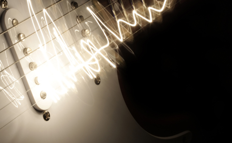 close-up-of-electric-guitar-with-white-lit-strings