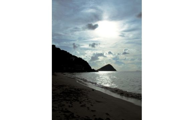 british-virgin-islands-deserted-moody-beach-silhouette-sunlight-breaking-through-clouds-onto-sea