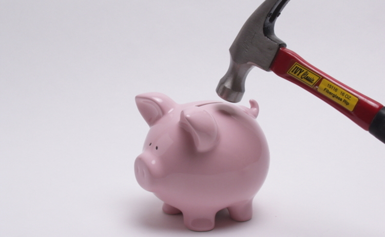A hammer about to smash a piggy bank