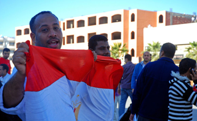 A man holding an Egypt flag during a demonstration