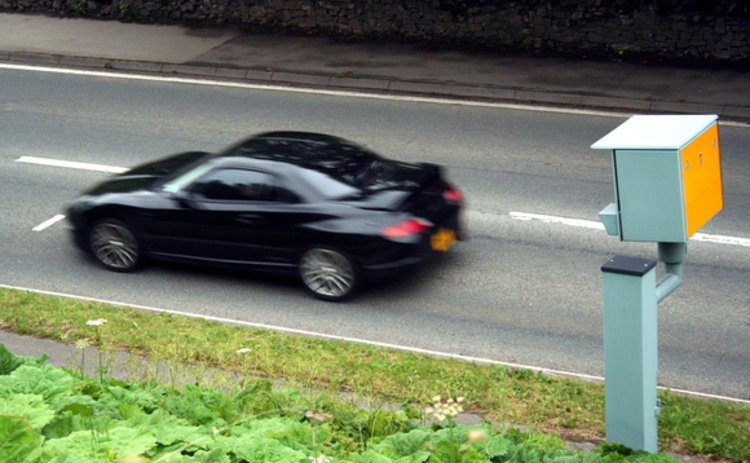 A black car passes a speed camera